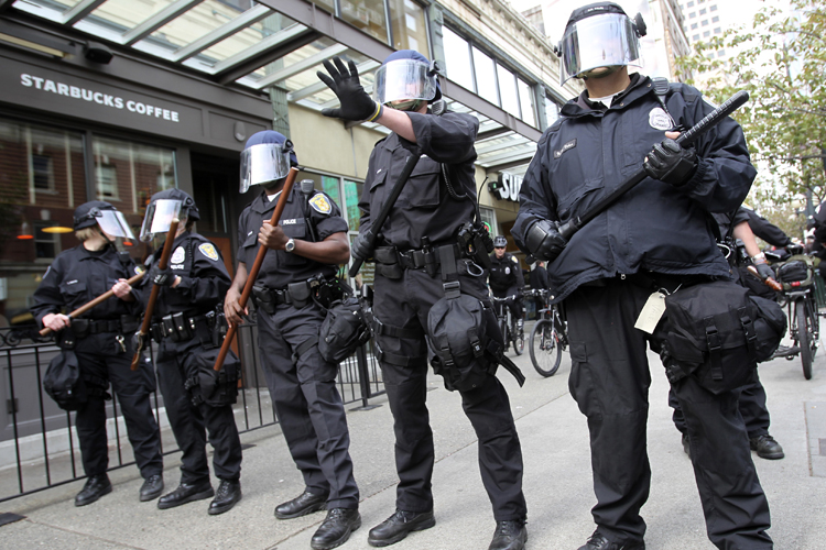 Seattle police officers wearing riot gear guard a Starbucks coffee shop during May Day demonstrations in Seattle